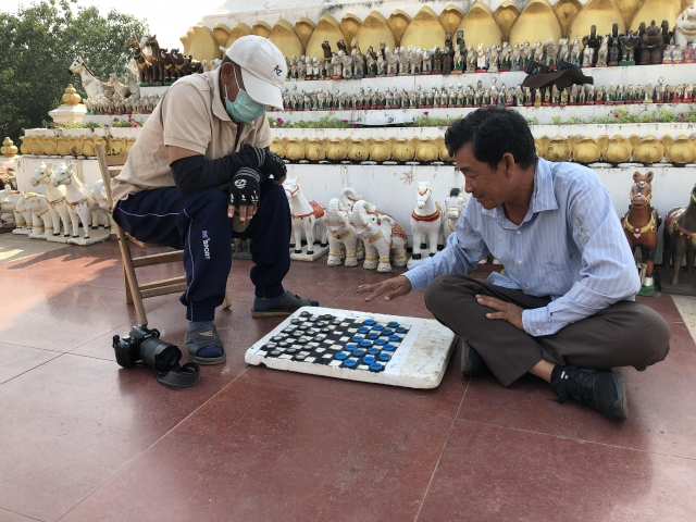 a couple of locals playing checkers with bottle caps